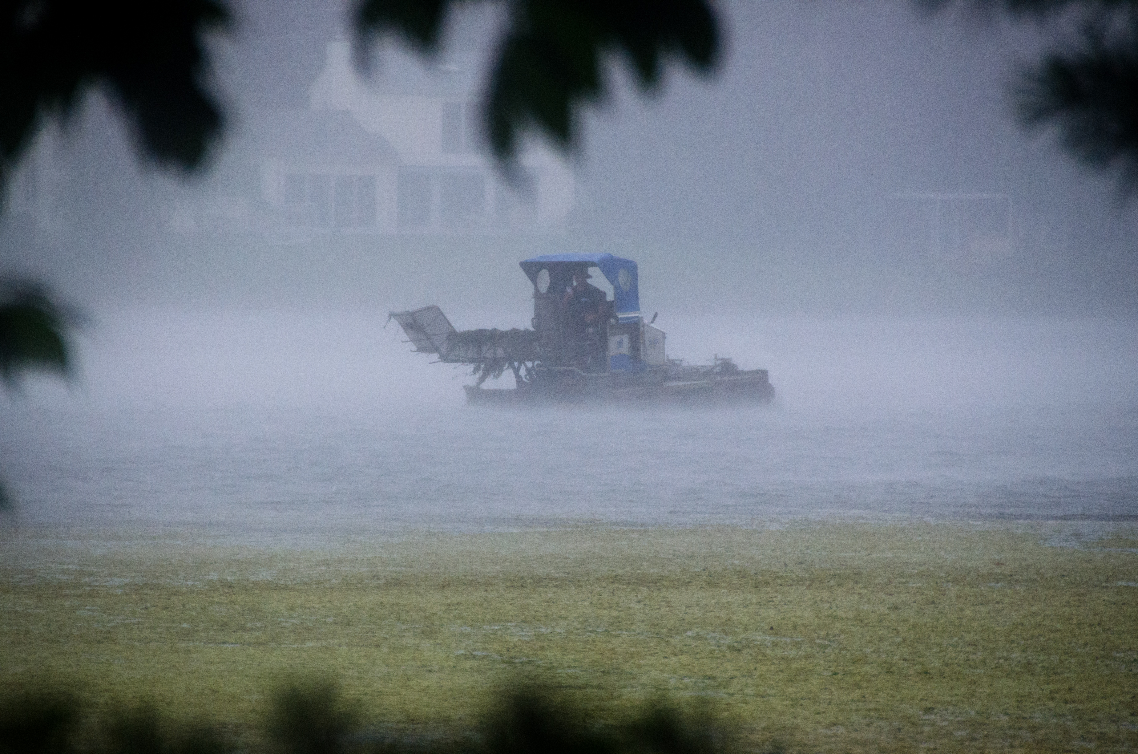 Harvester hurries back to land after a sudden thundershower cracks open the skies. (Photo by Rob Cummings)
